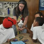 MickaCoo director introducing pigeon to animal shelter summer campers