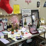A table of donated silent auction items at Holiday Party