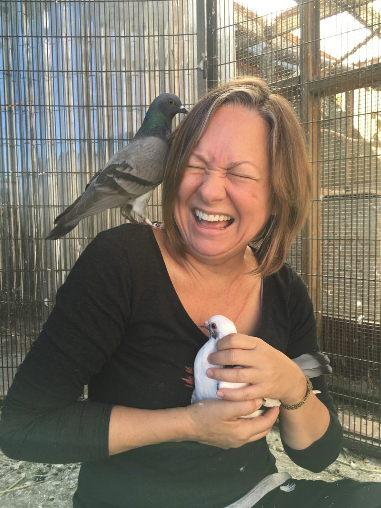 Laughing person with pigeon on her shoulder